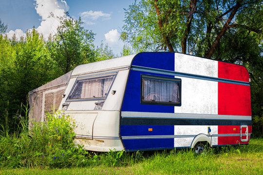 A car trailer, a motor home, painted in the national flag of  France stands parked in a mountainous. The concept of road transport, trade, export and import between countries.