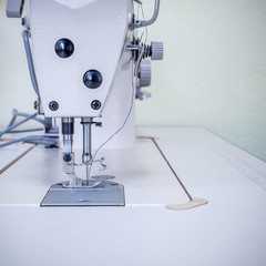 Sewing machine. In the foreground a mechanism with a needle and thread