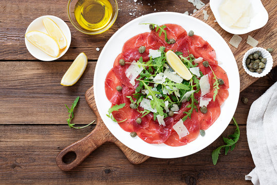 Beef Carpaccio cold appetizer with parmesan, capers and arugula on white plate.Top view.