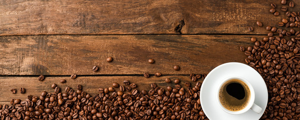 Black coffee cup with beans on retro wooden background with copyspace. Top view. Banner