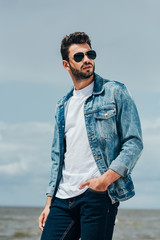 handsome man in denim jacket and sunglasses looking away