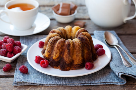 Chocolate marble bundt cake with a cup of tea on wooden background. Close up.