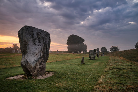 Stunning Summer sunrise landscape of Neolithic standing stones in English cluntryside with gorgeous light with slight background mist