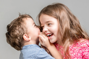 Boy in a blue shirt whispers in the ear a girl in a red dress on a gray background.