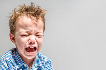 Crying little boy on a gray background .