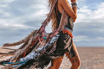 close up of young boho style woman on the beach at sunset Wall mural