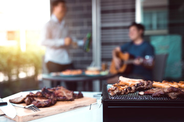 Close up grilled meats and various food on the grill and celebrations of friends who are playing guitar and sing together in their home.