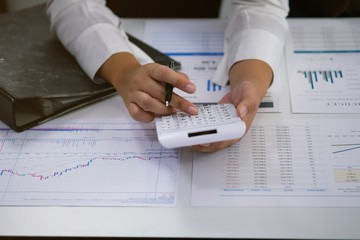 Businessman analyzing investment charts and pressing calculator buttons over documents. Accounting Concept.