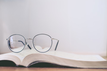 Reading thin frame glasses on book. Vintage style.