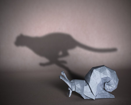 Concept of hidden potential. A paper figure of a snail that fills the shadow of a cheetah. 3D illustration