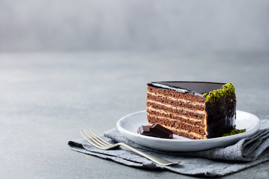 Chocolate cake on a white plate. Grey stone background. Copy space.