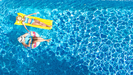 Children in swimming pool aerial drone view fom above, happy kids swim on inflatable ring donut and mattress, active girls have fun in water on family vacation on holiday resort Wall mural