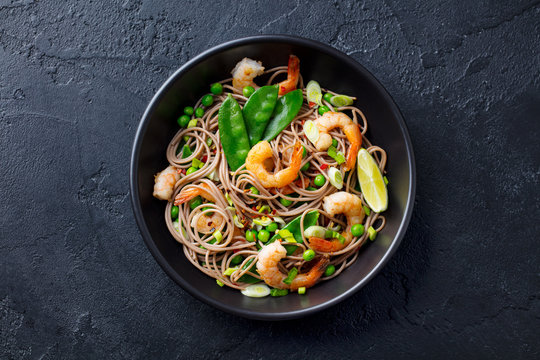 Stir fry noodles with vegetables and shrimps in black bowl. Slate background. Top view.