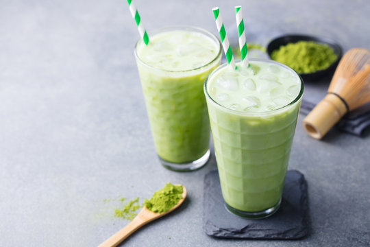 Matcha green tea ice latte with matcha powder and bamboo whisk. Copy space.