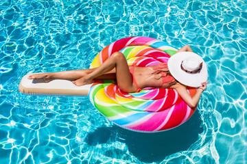 Junge, attraktive Frau im Bikini treibt auf einer Lolliförmigen Luftmatratze auf einem Swimming Pool