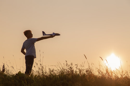Cute white kid playing happily outdoor with big toy plane during gold sunset time in summer landscape. Horizontal color photography.