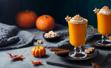 Pumpkin latte with spices. Boozy cocktail with whipped cream on slate board. Grey background. Copy space.