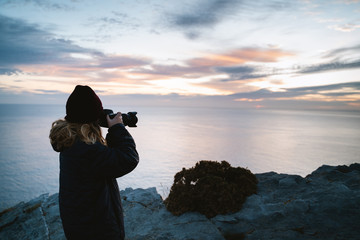 Photographer girl taking pictures during sunrise by the ocean