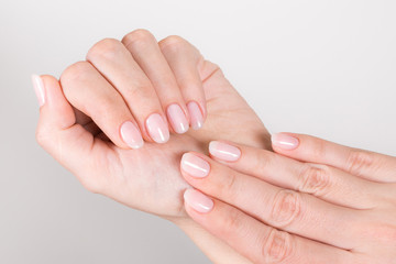 Closeup top view of beautiful natural pastel manicure at white hands of woman. Horizontal color photography.