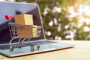 Brown paper boxs in a shopping cart with laptop keyboard on wood table on the public park background.Easy shopping with finger tips for consumers.Online shopping and delivery service concept.