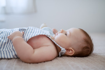 Side view of adorable baby boy lying on bed and waiting for his mother to pick him up.