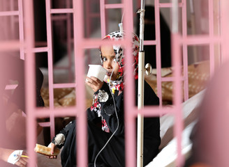 Girl looks from behind bars as she sits on bed at al-Sabeen hospital where she receives treatment in Sanaa