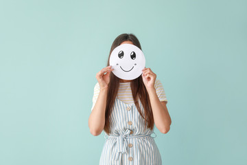 Woman hiding face behind sheet of paper with drawn emoticon on color background