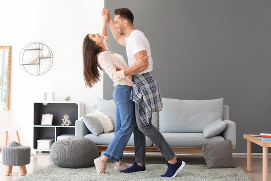 Happy young couple dancing at home