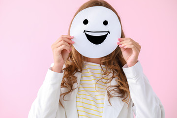 Woman hiding face behind  emoticon on color background