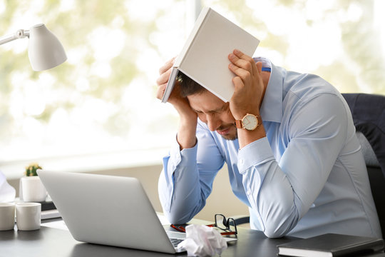 Stressed man at table in office