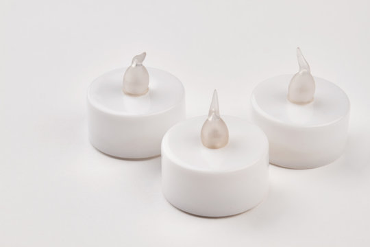 Wireless led candles with remote control. Three electronic flameless tea light candles on white background.