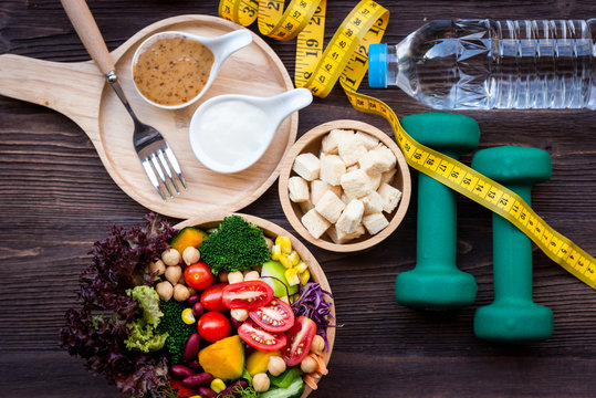 Fresh vegetable salad and healthy food for sport equipment for women diet slimming with measure tap for weight loss on wood background. Healthy Sport Concept