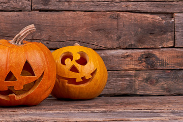 Funny Halloween pumpkins on wooden background. Halloween pumpkins with smiling faces. How to carve pumpkin for Halloween.