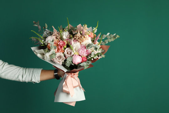 Man holding beautiful flower bouquet on green background, closeup view. Space for text