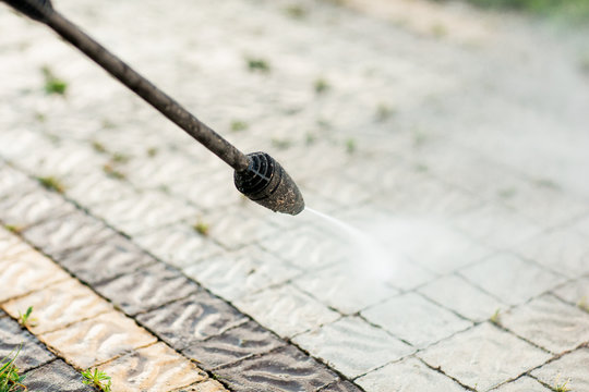 Close up photo of a cleaning a tile of grass in his yard. High pressure cleaning
