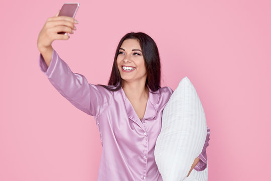 Cheerful woman taking selfie with pillow