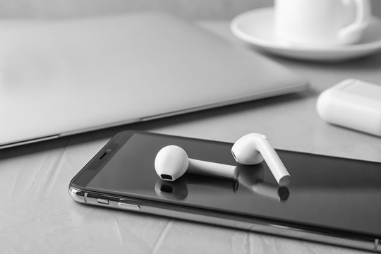 Modern wireless earphones and mobile phone on light grey stone table