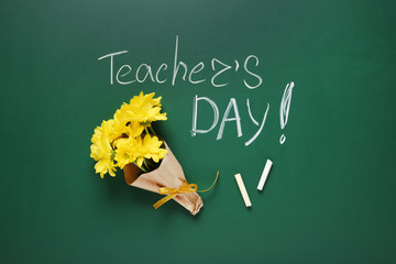 Flat lay composition with flowers and inscription TEACHER'S DAY on green chalkboard