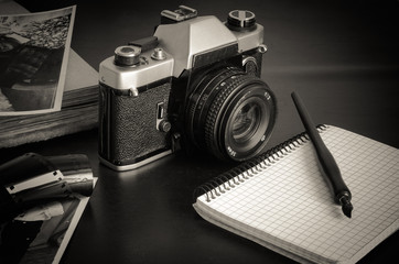 Closeup of a vintage camera on a dark table. Nearby to the metal camera is an old photo album, photographs, film and a notebook with a fountain pen. Eye level shooting. Soft focus. Monochrome photo