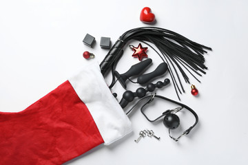 Christmas stocking with different sex toys on white background, top view