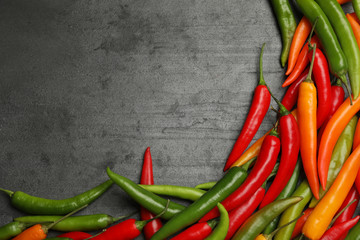In de dag Hot chili peppers Different ripe chili peppers grey table, flat lay. Space for text