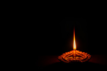 Happy Diwali. Background picture of traditional diya clay oil lamp lit at dark night on Diwali with...