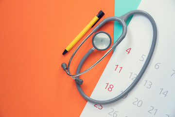 Top view of stethoscope and calendar on the color background, schedule to check up healthy concept