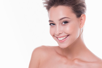 Portrait of young and beautiful smiling woman with clean and radiant skin of face and body posing on white background. Concept of care and cleaning procedures at home and in the salon. Place for text