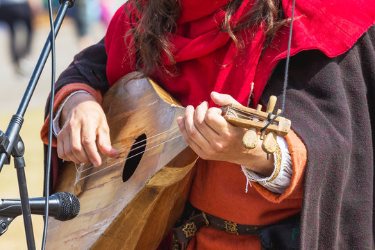 Musician performs a tune on a medieval musical plucked instrument that resembles a mandolin or lute_