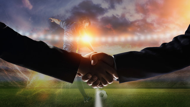 Image handshake with soccer field background.Business with football games
