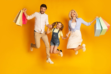 Happy Family Jumping Holding Shopping Bags Over Yellow Background