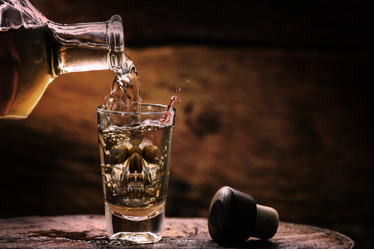 Drink bottle and glass with alcohol content. Image of translucent skull in glass. Alcoholism, addiction or poison concept.
