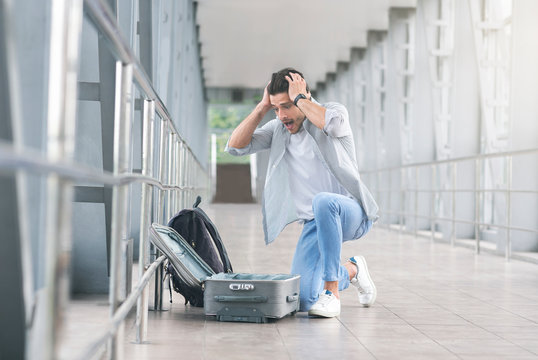 Desperate and shocked passenger checking his luggage at airport