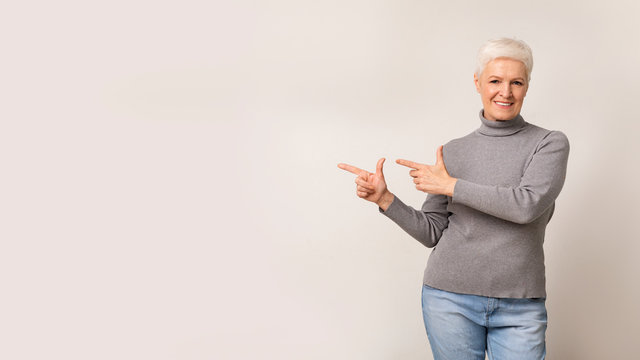 Beautiful elderly woman pointing away at free space